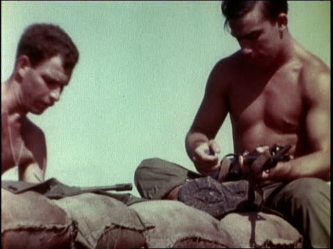 1960s montage a soldier cleaning his rifle with a friend / vietnam - gewehr stock-videos und b-roll-filmmaterial