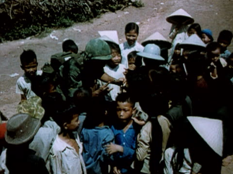 1960s MONTAGE American soldier giving candy to Vietnamese children / CU children smiling laughing / Vietnam