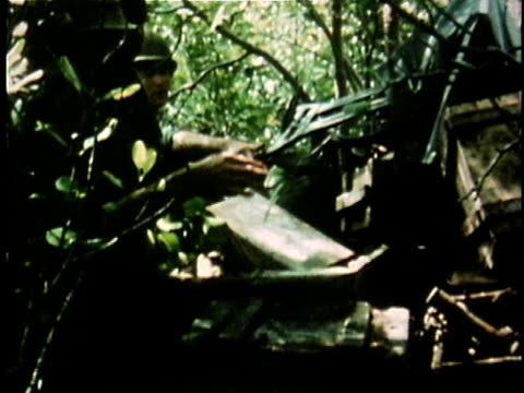 1960s MONTAGE American soldiers in jungle unpacking and unloading rocket ammunition during Vietnam War / Vietnam