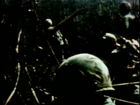 1960s MONTAGE American soldiers slowly advancing across jungle clearing as helicopter flies overhead / Vietnam