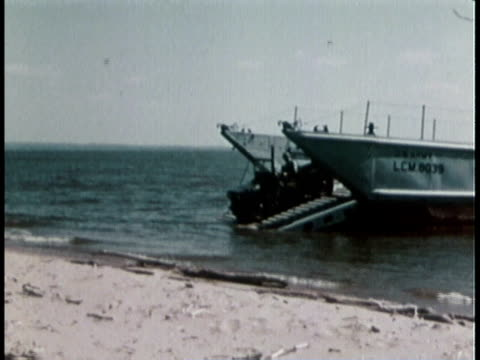 1960s MONTAGE Army jeep moves down ramp of amphibious LST boat and drives onto beach