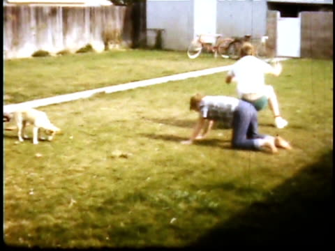1960s montage boys playing in back yard, leapfrogging and cartwheeling / lompoc, california, usa - hoppa bock bildbanksvideor och videomaterial från bakom kulisserna