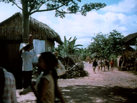 1960s montage ms children walking to school as man rings bell / cu man ringing bell / ms children gathering in classroom / vietnam - school bell stock videos and b-roll footage