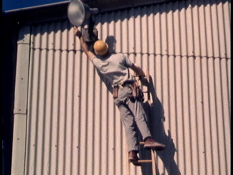 1960s MONTAGE Factory worker leaning precariously on ladder, trying to reach something to the side / United States