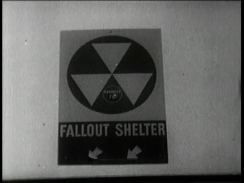 1960s MONTAGE Fallout shelter signs are posted everywhere