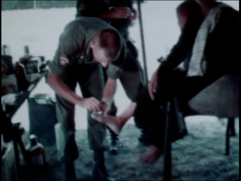 1960s montage first infantry division medic treating civilian woman's foot / vietnam - infantry stock videos & royalty-free footage
