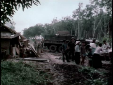 1960s montage first infantry division soldiers loading truck in village / vietnam - infanteri bildbanksvideor och videomaterial från bakom kulisserna