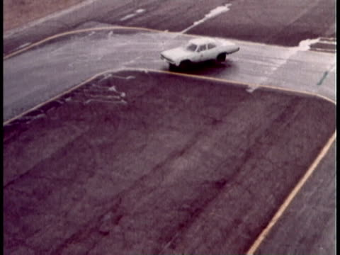 1960s montage man handling skidding car on track / united states - 横滑り点の映像素材/bロール