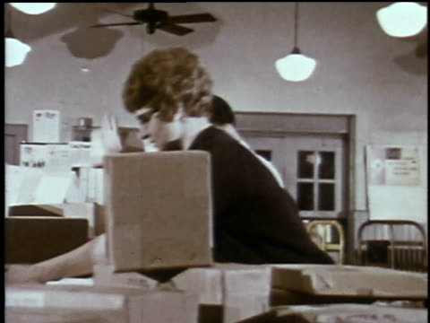 1960s montage postal employees sorting letters and packages and selling stamps / waterloo, iowa, united states - briefmarke stock-videos und b-roll-filmmaterial