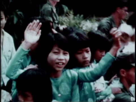 1960s montage santa claus making appearance for vietnamese children in military camp, while first infantry division soldiers watch and smile / vietnam - infantry stock videos & royalty-free footage