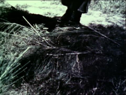 1960s montage soldier on patrol finding an enemy booby trap / vietnam - ブービートラップ点の映像素材/bロール