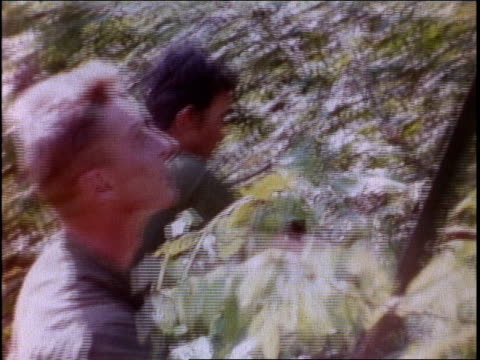 vídeos de stock, filmes e b-roll de 1960s montage soldiers hacking through dense vegetation walking through rice patty / vietnam - vadear