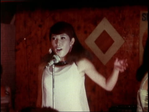 1960s montage soldiers in civilian clothing enjoying a girl band performing in a nightclub / vietnam - 横顔点の映像素材/bロール