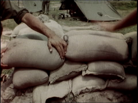 1960s montage soldiers reinforcing bunker positions with sandbags / vietnam - sandbag stock videos & royalty-free footage