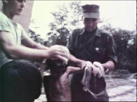 1960s MONTAGE US Marine Corps medics bathing a small boy / Vietnam