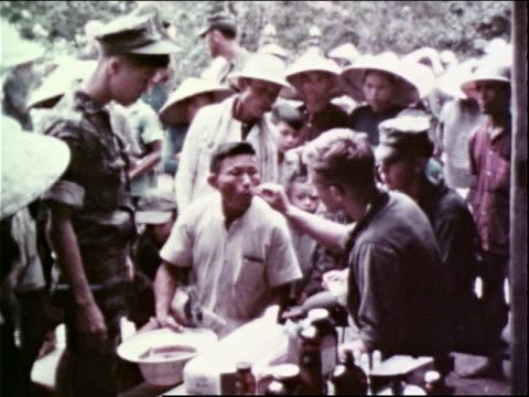 1960s MONTAGE US Marine Corps medics examining civilians in a village / Vietnam