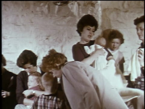 vídeos de stock e filmes b-roll de 1960s montage women and children sitting in fallout shelter in emergency test / plattsburgh new york united states - simulacro de emergência