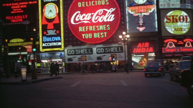 1960s WS POV Night street traffic with colorful neon signs / London, UK