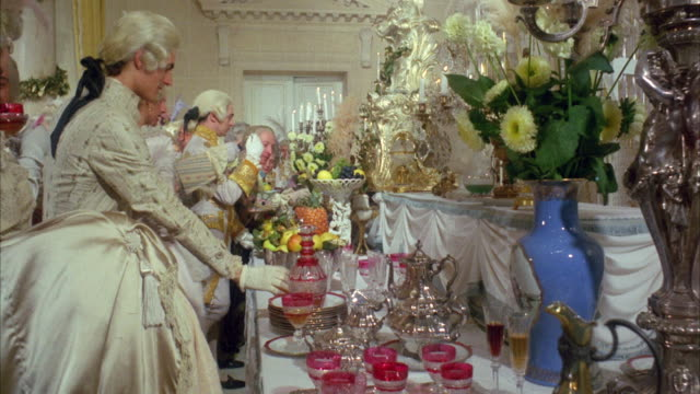 1960s ms palace ball with long buffet table loaded with food and drinks, guests along table - 18th century stock videos and b-roll footage