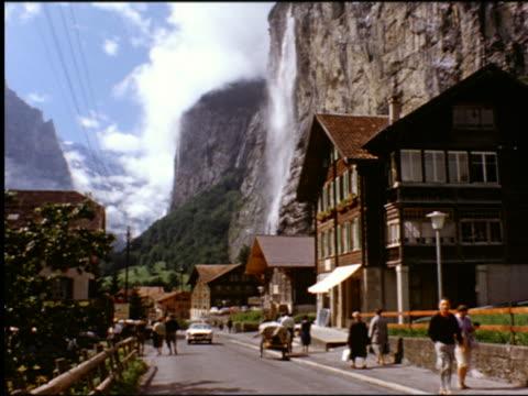 1960s people + car on village street with staubbach falls mountain waterfall / lauterbrunnen, switzerland - urlaubsort stock-videos und b-roll-filmmaterial