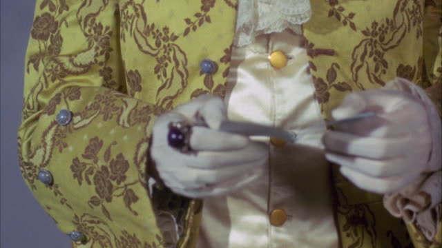 stockvideo's en b-roll-footage met 1960s cu pan people in ornate clothes passing folded note - 1960 1969