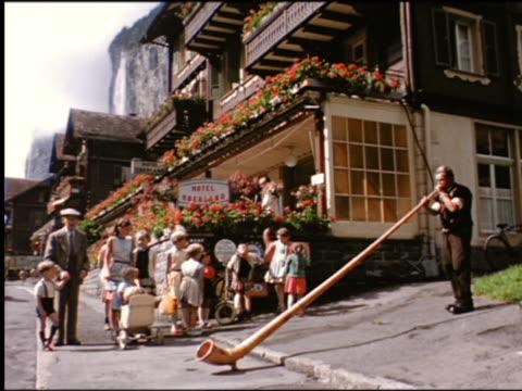 1960s people standing next to hotel watching man blow alpenhorn / switzerland - wind instrument stock videos & royalty-free footage