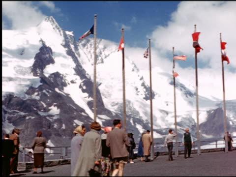 vidéos et rushes de 1960s people walking along flag-lined platform overlooking snowy alps (kaiser franz josefs hohe summit?) / grossglockner hochalpenstrasse, austria - austria