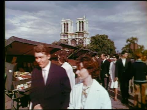 vidéos et rushes de 1960s people walking + looking at sidewalk vendor stands / notre dame in background / paris, france - 1960