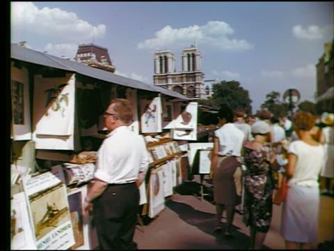 1960s people walking + looking at sidewalk vendor stands / notre dame in background / paris, france - market trader stock videos & royalty-free footage