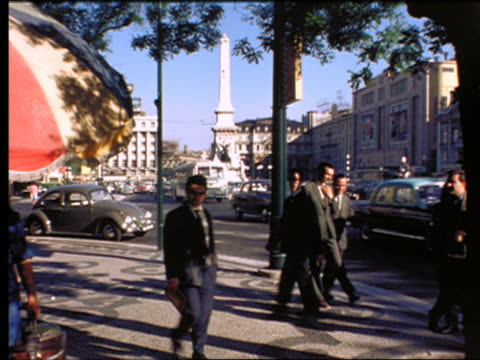 1960s people walking on sidewalk + traffic passing on city street / Lisbon, Portugal