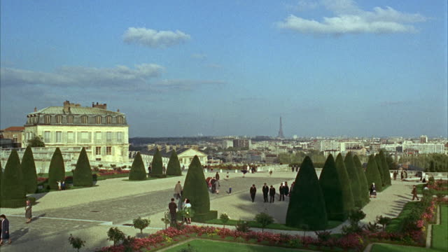 1960s ws people walking through garden, with cityscape / paris, france - 1960 stock-videos und b-roll-filmmaterial