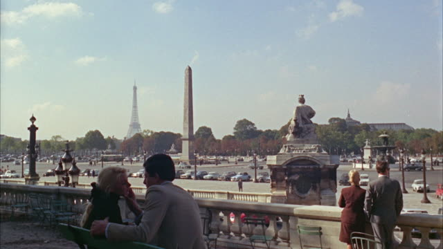 vídeos de stock e filmes b-roll de 1960s ws place de la concorde traffic with couple kissing in foreground / paris, france - obelisk