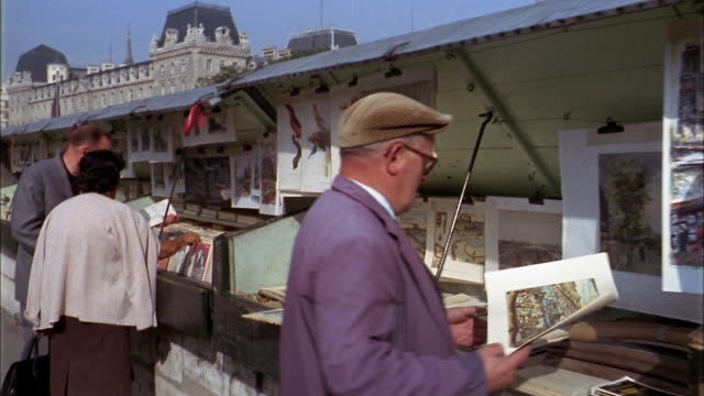 vidéos et rushes de 1960s point of view past street vendors stands of newspapers and books + artwork / paris - 1960