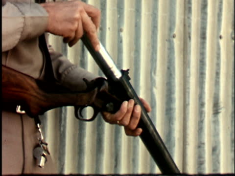 montage 1960s police officer loading tear gas cartridge into shotgun and firing gun at abandoned warehouse, california / usa - cartridge stock videos & royalty-free footage