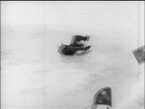 B/W 1960s REAR VIEW man on toboggan wiping out in competition / Villach Austria / educational