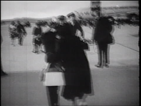 1960s rear view woman + child walking quickly to returning soldier / they hug + kiss / ca - homecoming stock videos & royalty-free footage