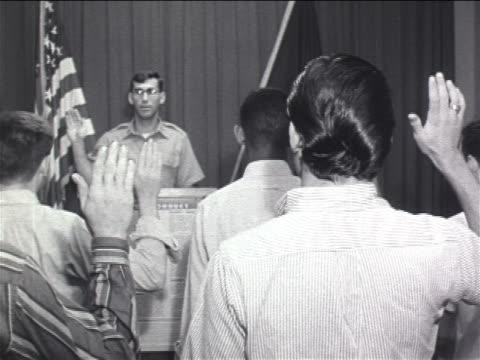 stockvideo's en b-roll-footage met 1960s rear view young men with hands raised taking oath of enlistment from officer / vietnam war - in dienst gaan