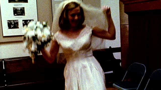 1960s REENACTMENT MS bride dancing around holding bouquet inside church