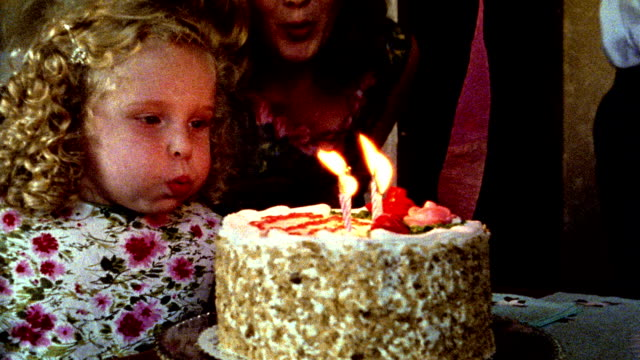 1960s REENACTMENT close up girl blowing at birthday cake candles / woman leaning over to help