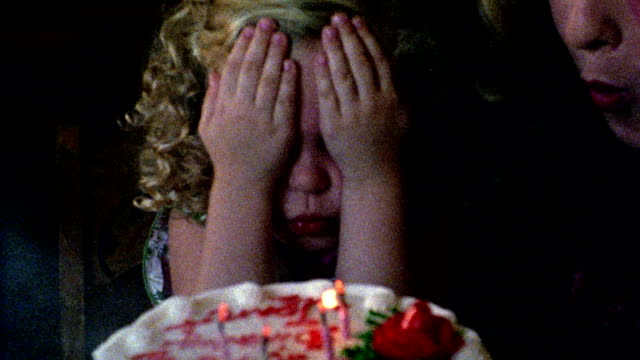 1960s REENACTMENT close up girl covering eyes with hands + blowing out candles on birthday cake