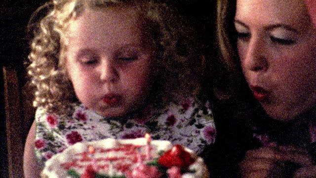 vídeos y material grabado en eventos de stock de 1960s reenactment close up pan grainy girl + woman blowing out candles on birthday cake / clapping - granulado