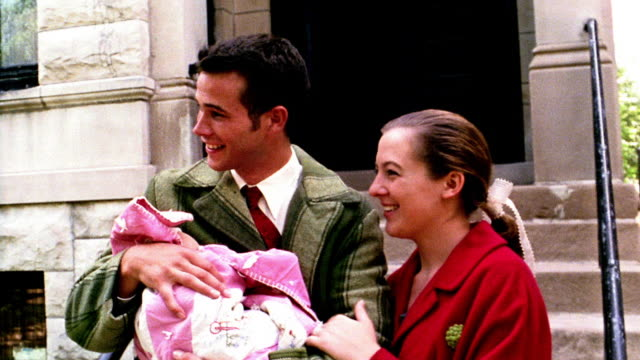 1960s reenactment ms couple posing with newborn in front of building / man holding baby - home movie video stock e b–roll