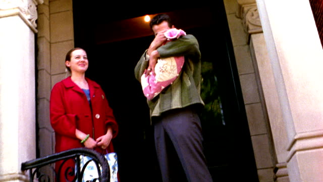 1960s REENACTMENT MS dolly shot couple with newborn posing outside door of building