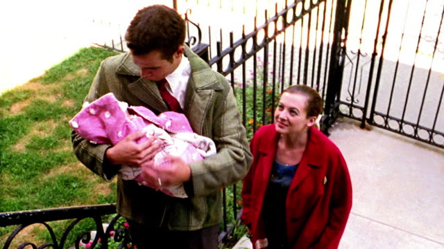 1960s REENACTMENT high angle MS couple climbing apartment stairs with newborn / man holding baby