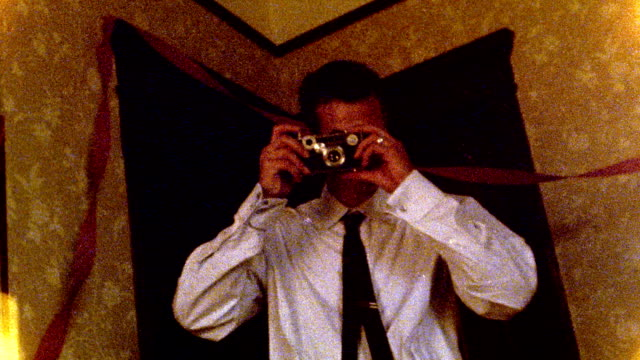 1960s REENACTMENT low angle MS man taking pictures at birthday party