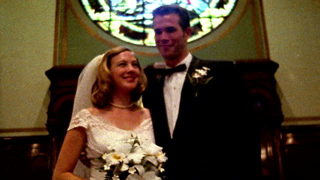 1960s REENACTMENT low angle MS tilt up tilt down bride + groom posing inside church
