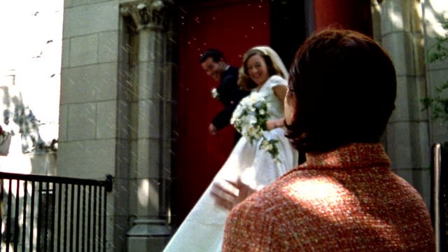 1960s reenactment slow motion ms bride + groom church leaving church / guests throwing rice - 異性のカップル点の映像素材/bロール