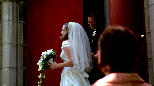vídeos de stock, filmes e b-roll de 1960s reenactment slow motion ms bride + groom church leaving church / guests throwing rice - bridesmaid