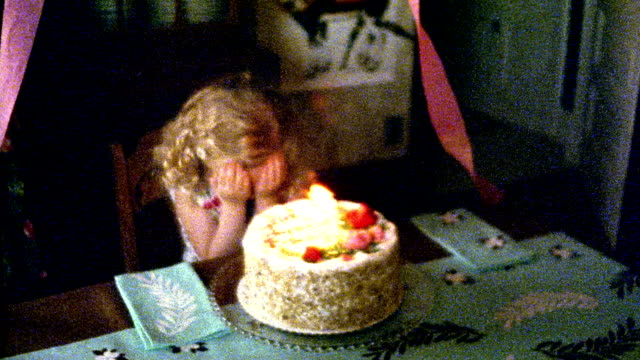 1960s REENACTMENT slow motion MS girl with eyes closed behind birthday cake