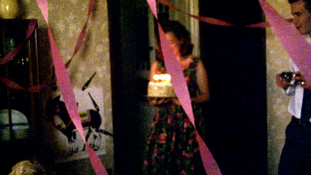 1960s reenactment slow motion wide shot woman bringing lit birthday cake to girl / man taking pictures - birthday candle stock videos & royalty-free footage